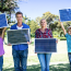 Family Holding Solar Panels Outdoors